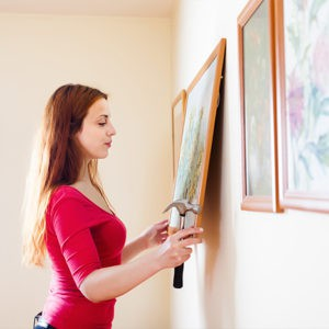 Lady hanging Pictures